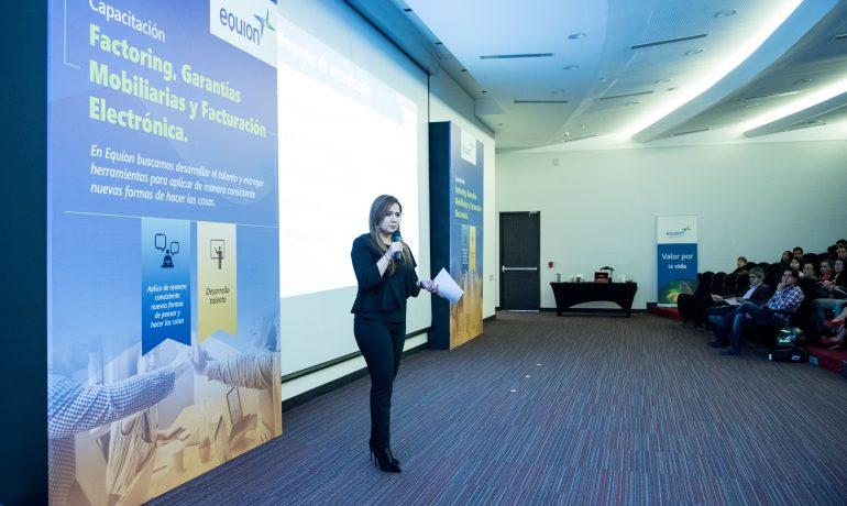 Imagen: Mujer trabajadora de Equión en frente de varias personas en un salón de conferencias
